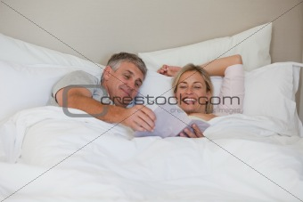 Couple reading a book in their bed