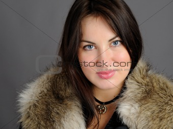 Beautiful brunette woman in elegant animal fur jacket