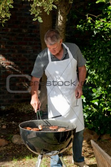 Handsome man having a barbecue in the garden