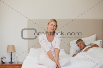 Woman looking at the camera while her husband is sleeping