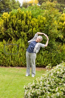 Retired  woman doing her streches in the garden
