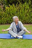 Mature woman doing her stretches in the garden