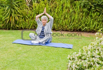 Senior woman doing her streches in the garden