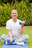 Retired man doing his exercises in the garden