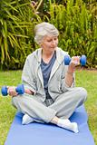 Retired woman doing her exercises in the garden