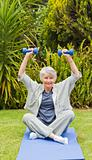 Retired woman doing her exercises in the garden
