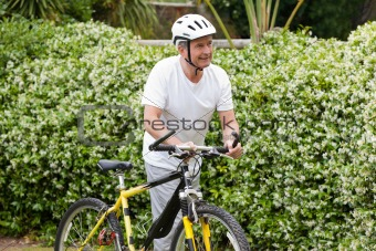 Mature man walking with his mountain bike
