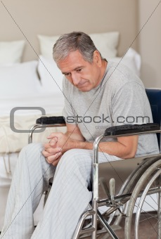 Thoughtful senior man in his wheelchair