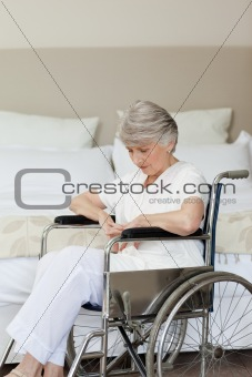 Senior woman asleep in her wheelchair at home