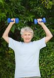 Mature woman doing her exercises in the garden