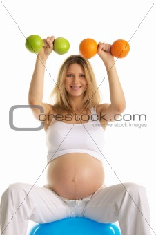 pregnant  is engaged in fitness dumbbells fruit