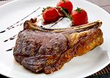 Grilled meat ribs on white plate with tomatoes