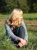 young blond woman is sitting on a grass