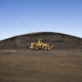 Bulldozer and dirt mound.