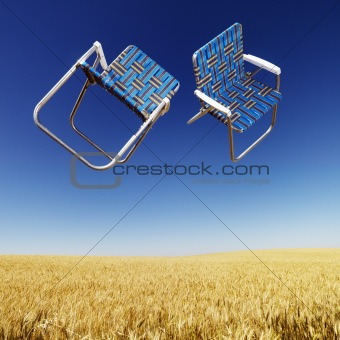 Lawn chairs over wheat field.