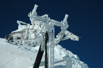 A ski lift covered with fresh snow looks like frozen