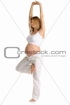 Pregnant woman practicing yoga, standing