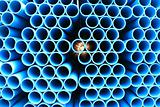 blue pipes stacked in construction site, pattern closeup