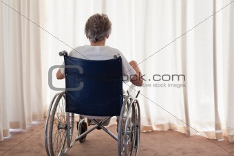 Mature woman in her wheelchair with her back to the camera at ho