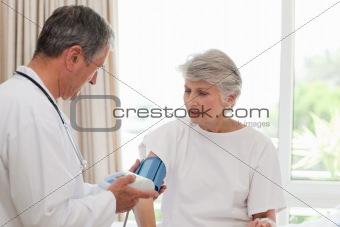 Mature doctor taking the blood pressure of his patient