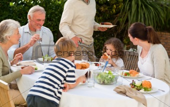 Adorable family eating in the garden