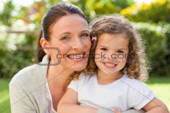 Mother with her daughter looking at the camera in the garden