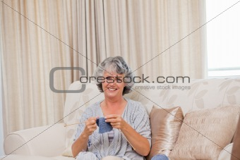 Retired woman knitting at home