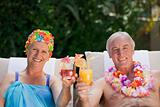 Mature couple drinking a cocktail  beside the swimming pool