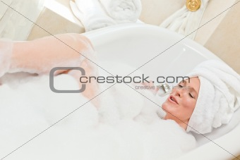 Charming woman taking a bath with a towel on her head