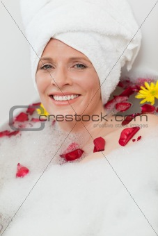 Relaxed woman taking a relaxing bath with a towel on her head