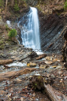 Waterfall and brook in mountain forest ravine