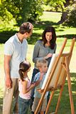 Family painting together in the park