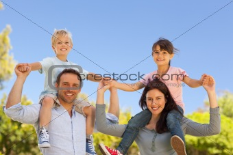 Parents giving  children a piggyback 