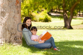 Mother with her daughter looking at their album photo