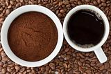 Coffee power in bowl and coffee in cup on top of coffee beans