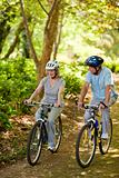 Elderly couple mountain biking outside
