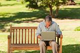 Elderly man working on his laptop in the park