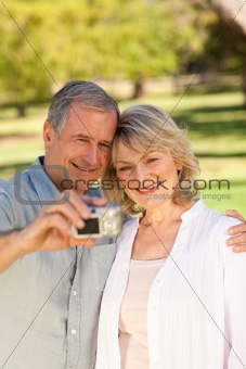 Elderly couple taking a photo of themselves in the park