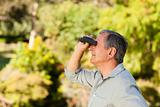 Senior man looking at the sky with his binoculars