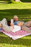 Woman reading while her husband is sleeping in the park