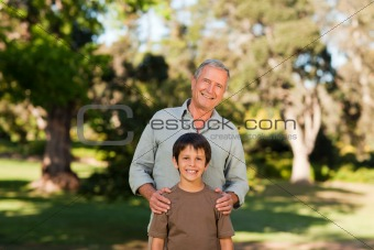 Grandfather with his grandson looking at the camera in the park