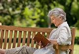 Retired woman reading a book on the  bench