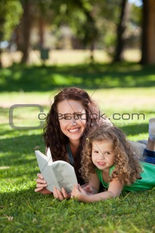 Woman with her daughter reading a book