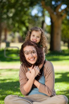 Woman hugging her daughter in the park