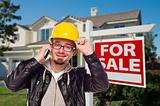 Contractor in Hard Hat in Front of House and For Sale Real Estate Sign.