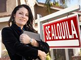 Proud, Attractive Hispanic Female Agent In Front of Spanish Se Alquila Real Estate Sign and House.