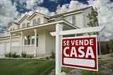 Se Vende Casa Spanish Real Estate Sign and House and Blue Sky with Clouds.