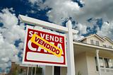 Vendido Se Vende Casa Spanish Real Estate Sign and House and Blue Sky with Clouds.