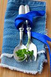 Spoon and fork in textilein  blue  napkin with a sprig of parsley