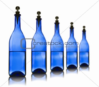 Five blue glass bottles with water